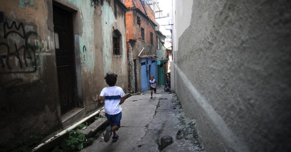 9.abr.2015 - Crianças brincam em viela no Complexo do Alemão, na zona norte do Rio de Janeiro. No dia 2 de abril, o menino Eduardo de Jesus Ferreira, 10, foi morto por um tiro de fuzil na porta de casa durante uma ação da Polícia Militar. A foto foi feita na quinta-feira (9)