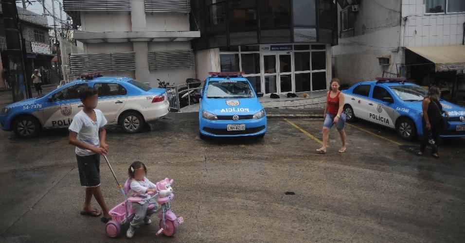 9.abr.2015 - Crianças brincam próximo a policiais em rua no Complexo do Alemão, na zona norte do Rio de Janeiro. No dia 2 de abril, o menino Eduardo de Jesus Ferreira, 10, foi morto por um tiro de fuzil na porta de casa durante uma ação da Polícia Militar. A foto foi feita na quinta-feira (9)