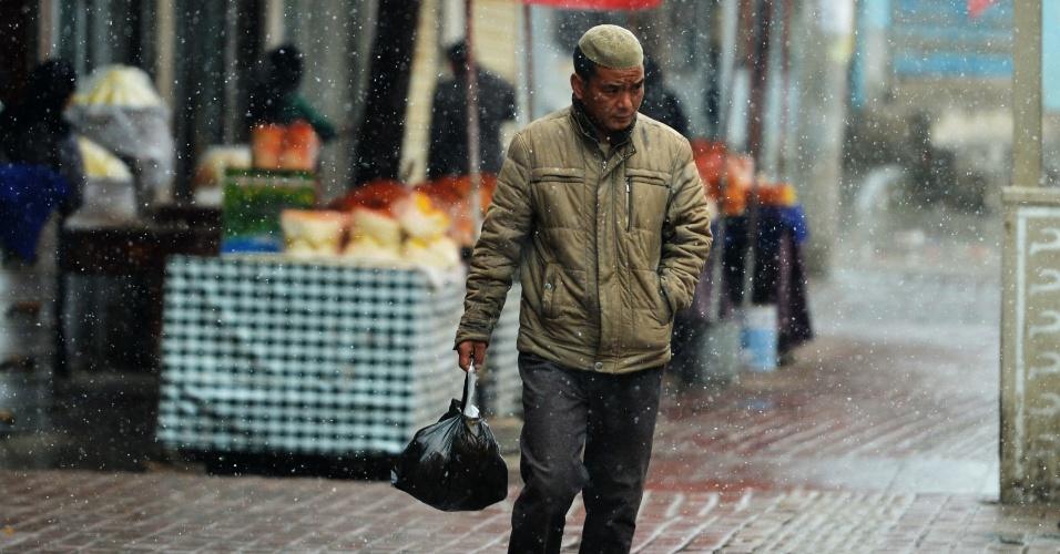 18.abr.2015 - Chinês caminha sob nevasca por rua do condado de Dongxian, na região central da China, neste sábado (18). Uma tempestade de neve inesperada atingiu a região no início da primavera no hemisfério norte