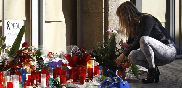 Mulher deixa flores em frente à escola onde um adolescente matou um professor