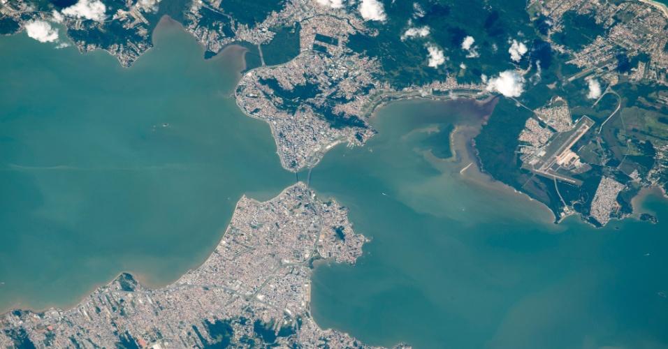27.abr.2015 - Imagem feita por astronautas da Estação Espacial Internacional (ISS, na sigla em inglês) registra a cidade de Florianópolis (SC). No centro da foto é possível ver as pontes que dão acesso à ilha, na região oeste, e na região inferior direita, o aeroporto Internacional Hercílio Luz. Próximo ao aeroporto a foto capta uma água marrom, saída de um pequeno córrego. De acordo com a Nasa, em muitas imagens da zona costeira é possível observar a poluição das cidades. A imagem foi feita em 10 de abril e divulgada nesta segunda-feira (27)