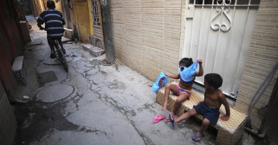 28.abr.2015 - Ciclista passa por beco da comunidade Roquette Pinto, uma das 16 do Complexo de Favelas da Maré, na zona norte do Rio de Janeiro. A favela está ocupada pela PM desde o dia 1º de abril e vai receber a primeira UPP (Unidade de Polícia Pacificadora) da Maré