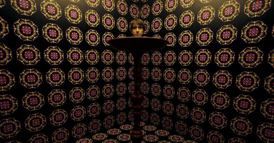 1.mai.2015 - Mesa com cabeça ou cabeça com corpo de mesa? Jonathan Aubrey, 25, visita a exposição ''Espelhos da Invisibilidade'', que brinca com ilusões de ótica no Museu de Ciência de Hong Kong