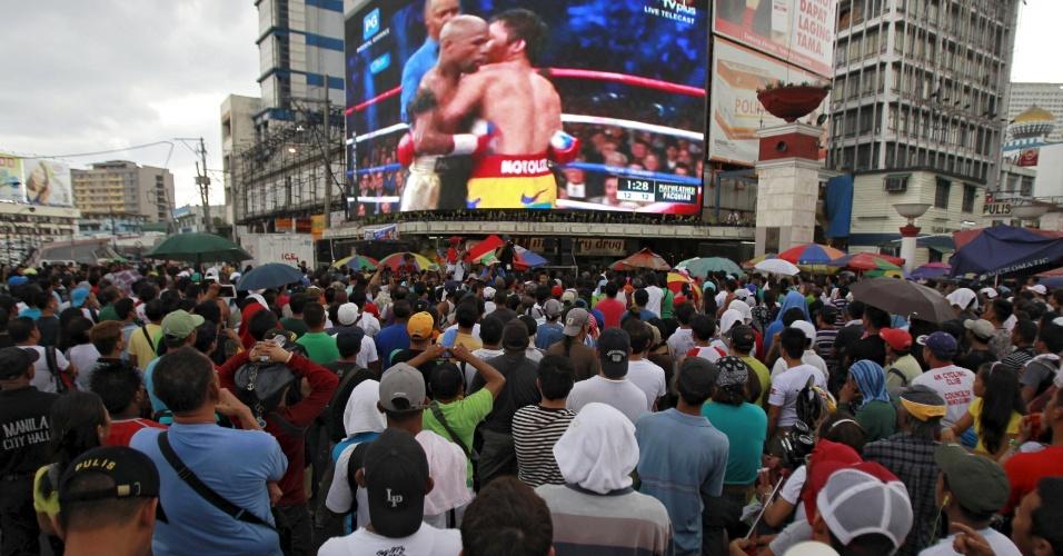 3.mai.2015 - Fãs assistem à luta de boxe entre o filipino Manny Pacquiao (à direita) e o americano Floyd Mayweather em telão no centro de Manila, capital das Filipinas. Chamada de
