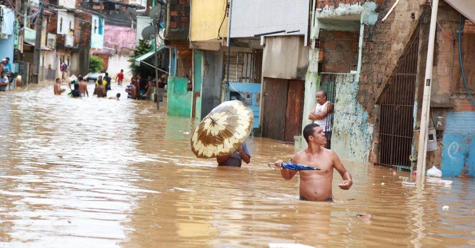 10.mai.2015 - Moradores atravessam rua alagada no bairro do Imbuí, em Salvador, neste  domingo (10). A chuva que atinge a cidade desde a noite de sexta-feira (8) já provocou desabamentos e quedas de árvores