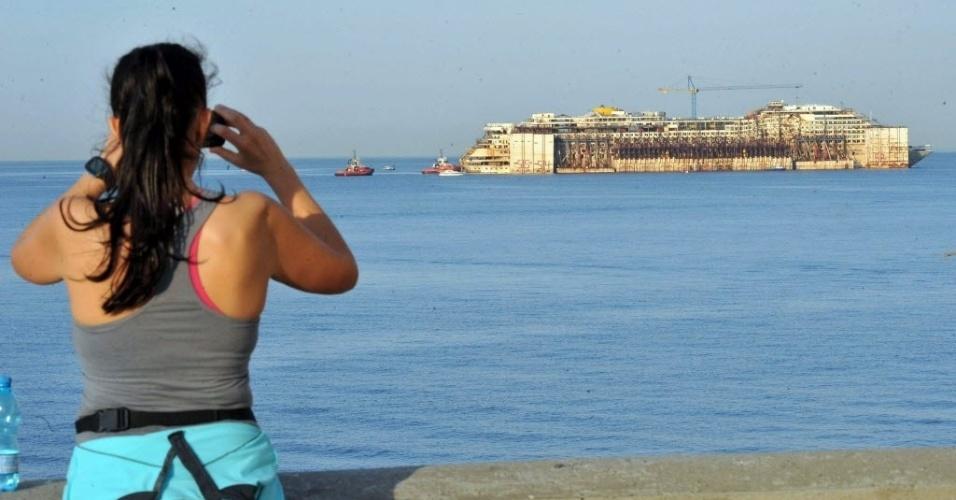 12.mai.2015 - Mulher tira fotos do navio Costa Concordia da ponte de Gênova, na Itália, nesta terça-feira (12). A embarcação começou a ser removida na segunda-feira (11) do estaleiro de Prà Voltri de Gênova até outro porto próximo, onde será completamente desmontado. O Costa Concordia encalhou em janeiro de 2012 próximo a ilha italiano de Giglio, causando a morte de 32 pessoas