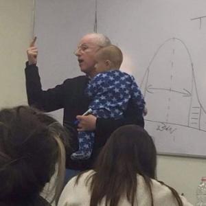 O professor Sydney Engelberg segura no colo bebê de estudante