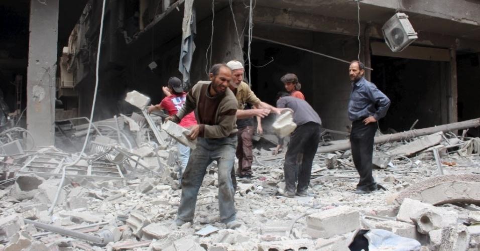14.mai.2015 - Civis removem escombros de um local destruído após ataques aéreos de forças leais a ditador sírio Bashar Assad, em Damasco, Síria