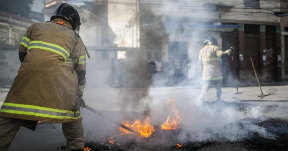 15.mai.2015 - Bombeiros tentam controlar chamas de barricada feita durante protesto contra a morte de dois moradores da comunidade do São Carlos, no Estácio, na zona norte do Rio de Janeiro (Brasil). Desde o dia 8 de maio, pelo menos dez pessoas foram mortas em uma guerra de facções na região