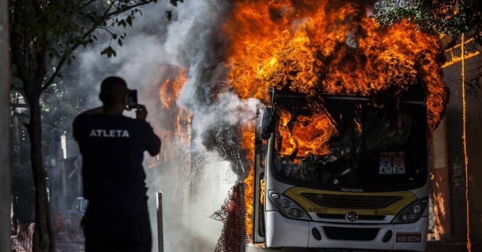 15.mai.2015 - Morador tira foto de um ônibus em chamas durante protesto contra a morte de dois moradores da comunidade do São Carlos, no Estácio, na zona norte do Rio de Janeiro (Brasil). Desde o dia 8 de maio, pelo menos dez pessoas foram mortas em uma guerra de facções na região