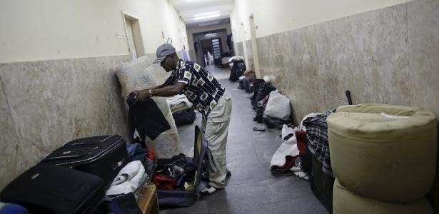 20.mai.2015 - Imigrante haitiano organiza suas roupas na Igreja Católica Nossa Senhora da Paz, onde vive com outros conterrâneos, no bairro do Glicério, em São Paulo