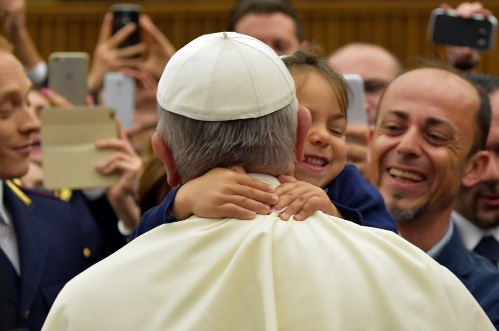 21.mai.2015 - Uma menina abraça o papa Francisco durante uma reunião com famílias de policiais mortos em serviço, no Vaticano