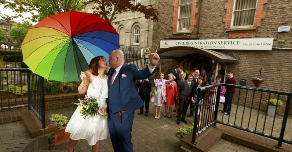 22.mai.2015 - A recém-casada Anne Cole segura um guarda-chuva símbolo do orgulho gay enquanto beija seu marido Vincent Fox depois casarem em um cartório em Dublin no dia em que a Irlanda realizada um referendo sobre o casamento entre pessoas do mesmo sexo