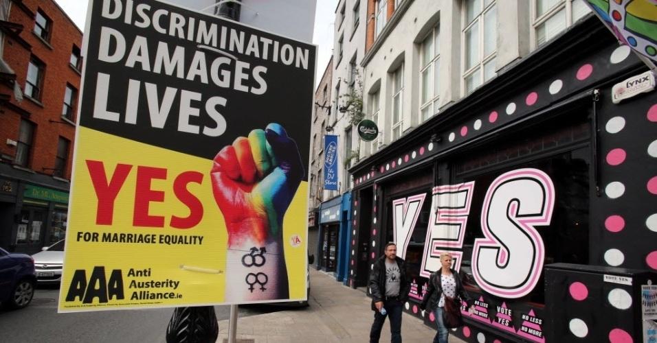 22.mai.2015 - Pedestres caminham entre cartazes em favor do casamento entre pessoas do mesmo sexo em Dublin, capital da Irlanda. Nesta sexta-feira (22), o país realiza um referendo para decidir sobre a legalidade do casamento entre pessoas do mesmo sexo