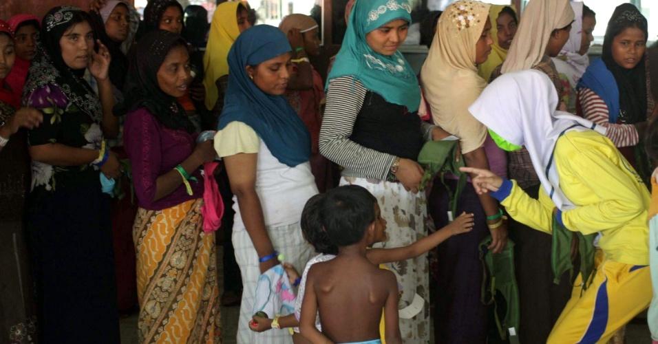 23.mai.2015 - Imigrantes da etnia muçulmana refugiados após deixar Bangladesh e Mianmar conversam com voluntária em fila para receber auxílio humanitário em abrigo na província de Aceh (Indonésia), neste sábado (23). Malásia e Indonésia concordaram no início da semana a receber os milhares de refugiados que deixam seus países fugindo da violência sectária