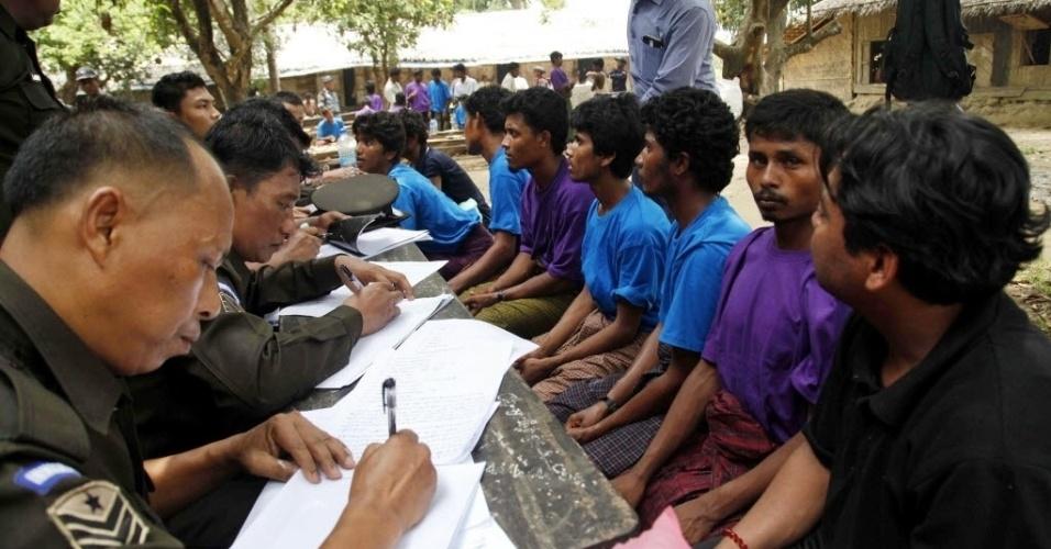Muculçanos da minoria rohingya vindos de Bangladesh são inspecionados por funcionários da imigração de Miamar em um campo de refugiados temporário neste sábado (23). Eles foram resgatados pela marinha do país. Autoridades da Malásia e da Indonésia disseram que passarão a ajudar milhares de imigrantes rohingya presos em barcos de traficante de pessoas. Os rohingyas dizem que sofrem discriminação em Mianmar, que não os reconhece como um dos grupo étnico oficial