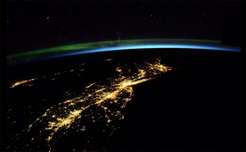 """25.mai.2015 - O astronauta Terry Virts, a bordo da Estação Espacial Internacional (ISS, na sigla em inglês), publicou uma imagem onde a Terra aparece """"envolvida"""" pela luz da aurora boreal"""