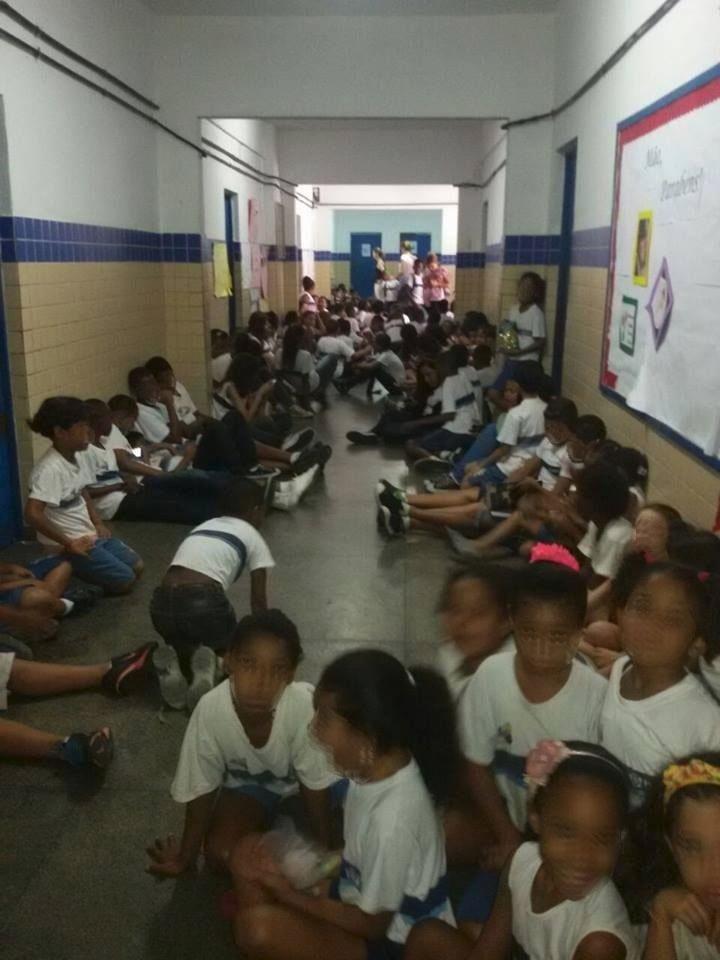 26.mai.2015 - Alunos da Escola Municipal Monsenhor Alves Rocha, no Parque Proletário, na Penha, zona norte do Rio de Janeiro, aparecem sentados no corredor da unidade em foto divulgada nesta terça-feira (26) pelo Coletivo Papo Reto. As crianças foram levadas ao local para se protegerem de um tiroteio que acontecia fora da escola