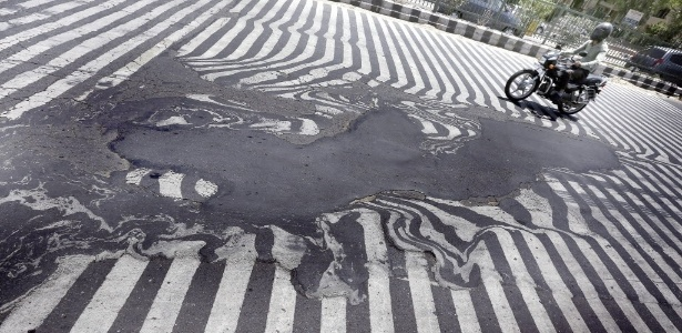 Motociclista passa perto de asfalto que derreteu por causa das altas temperaturas em Nova Déli, na Índia