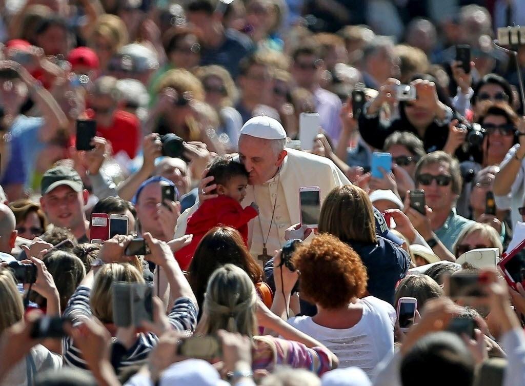 27.mai.2015 - Papa Francisco beija criança na praça de São Pedro, no Vaticano, durante a audiência geral