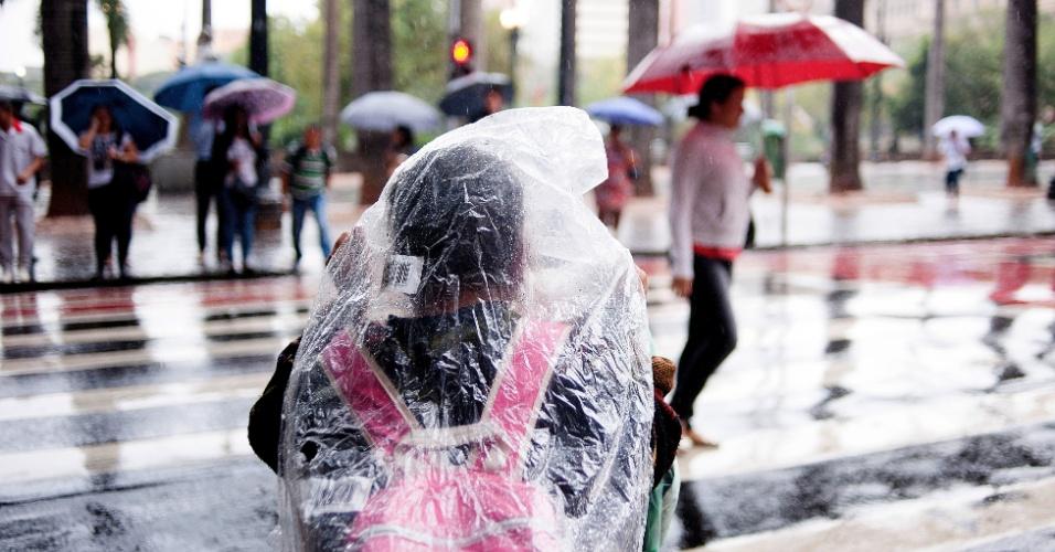 28.mai.2015 - Pedestres se protegem da chuva com capa e guarda-chuva, na praça da Sé, no centro de São Paulo