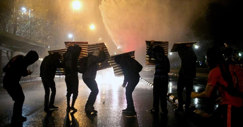 29.mai.2015 - Manifestantes se escondem na noite desta quinta-feira (28) de jato de água disparado pela polícia durante manifestação em Santiago (Chile) contra a violência policial e de apoio a Rodrigo Aviles, um estudante ferido em 21 de maio após outro protesto de estudantes. Aviles sofreu uma lesão na cabeça quando a polícia disparou canhões de água contra manifestantes, e está em estado grave em um hospital de Valparaiso