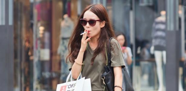 Garota fuma em área comercial em Pequim, na China, em foto tirada em junho de 2014. A partir da próxima segunda-feira (1º) estará proibido fumar nos locais públicos fechados na cidade