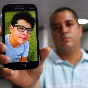 Christiano Britto, tio da vítima, mostra foto de Pedro, 18, esfaqueado no trem