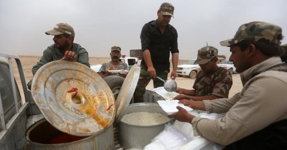1º.jun.2015 - Combatentes xiitas iraquianos distribuem alimentos na linha de frente de Tharthar, na fronteira com a província de Anbar. Um ataque suicida com um veículo blindado cheio de explosivos contra uma base da polícia iraquiana no noroeste de Bagdá matou pelo menos 37 pessoas, segundo autoridades