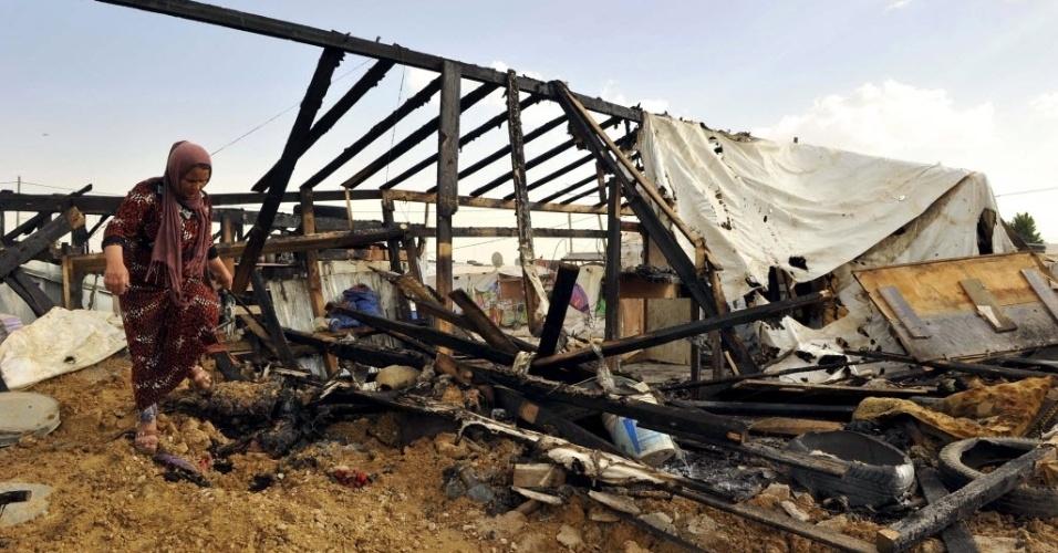1.º.jun.2015 - Síria caminha perto dos restos de tendas que foram queimadas em um campo de refugiados em Bekaa, no Líbano, nesta segunda-feira (1º). Pelo menos seis pessoas morreram quando dezenas de tendas pegaram fogo, segundo testemunhas. Cerca de 160 dos 300 barracos, que abrigavam 600 pessoas, foram queimados e várias pessoas estão desaparecidas. A causa do incêndio ainda é desconhecida