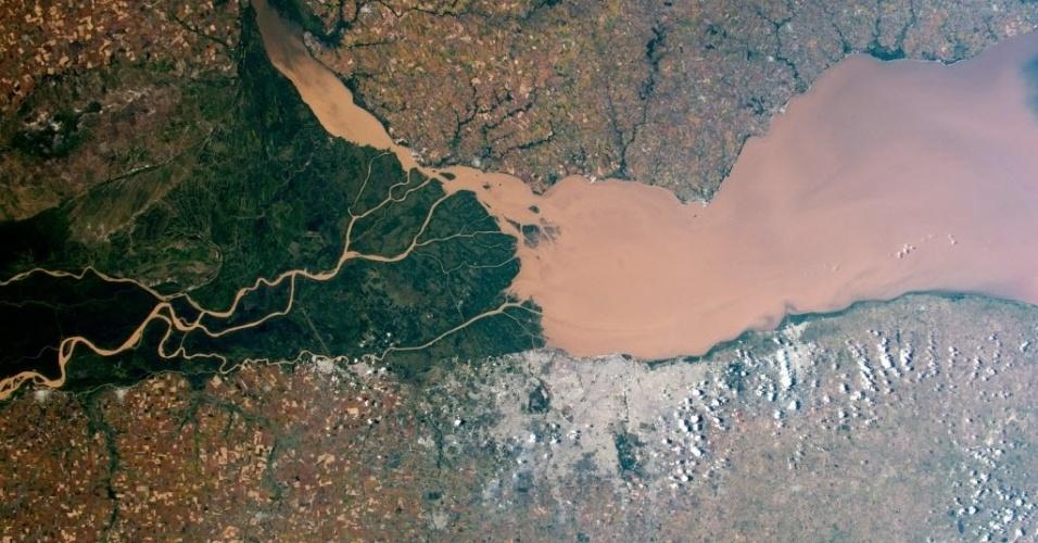 2.jun.2015 - Astronautas a bordo da Estação Espacial Internacional (ISS, na sigla em inglês) capturam imagem do rio Paraná, na costa da Argentina. O Paraná, o segundo maior rio da América do Sul depois do Amazônia, derrama a água no rio da Prata. A parte cinzenta da imagem é a capital da Argentina, Buenos Aires. Diversos espaços agrícolas circundam a cidade o rio