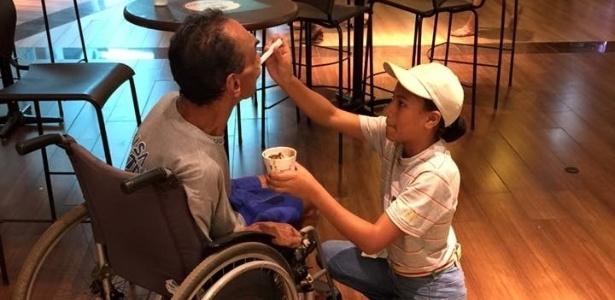 Funcionária do McDonald's Lawane Rodrigues ajuda José Avelino a comer sorvete em shopping center de Uberlândia (MG)