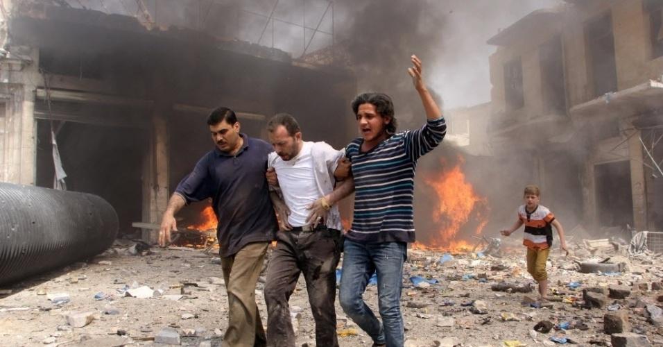 3.jun.2015 - Homens ajudam um ferido após um atentando feito por forças leais ao ditador sírio Bashar Assad, em Aleppo, Síria. Pelo menos 24 pessoas morreram, entre elas oito crianças, durante os bombardeios desta quarta-feira (3)