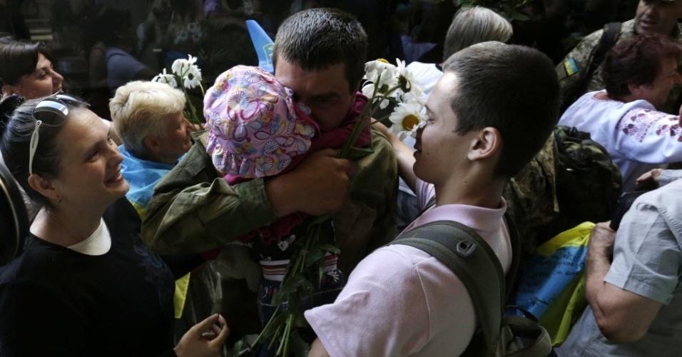 5.jun.2015 - De volta de Donetsk, onde o Exército da Ucrânia enfrenta rebeldes pró-Rússia, soldado ucraniano é abraçado por familiares em estação de trem em Kiev, capital do país