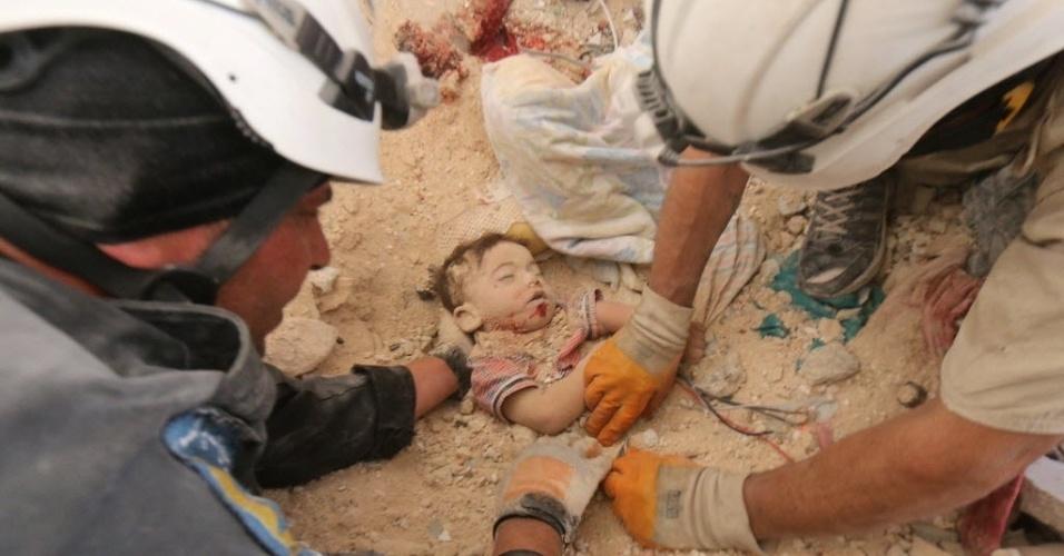 5.jun.2015 - O corpo de um bebê é resgatado de ruínas de casa bombardeada por forças sírias em Aleppo, no norte da Síria, nesta sexta-feira (5). Três membros de uma família, o pai, a mãe e a criança, morreram no bombardeio