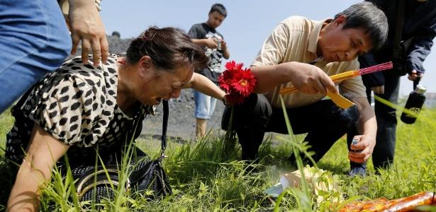 """Parente de passageiro do navio """"Estrela do Oriente"""" chora às margens do rio Yang Tsé, no centro da China"""