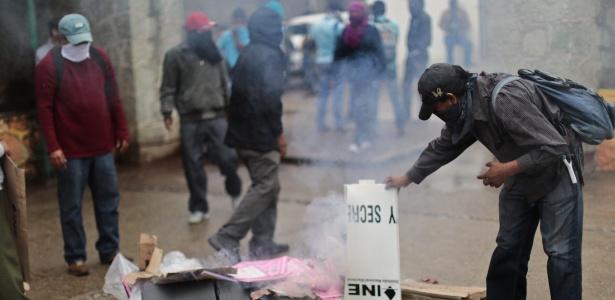 Manifestantes queimam urna no município de Tixtla, em Guerrero, no sul do México, durante a eleição legislativa deste domingo (7)
