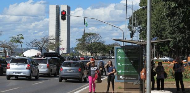 8.jun.2015 - Passageiros esperam ônibus em parada na Esplanada dos Ministérios, em Brasília, com o prédio do Congresso Nacional ao fundo. A greve dos rodoviários na capital federal atinge 1 milhão de pessoas nesta segunda-feira