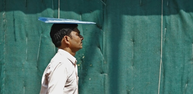 8.jun.2015 - Homem coloca pasta sobre a cabeça para se proteger do sol forte em Nova Déli, capital da Índia. A onda de calor, com temperaturas de até 50ºC, matou milhares de pessoas neste ano