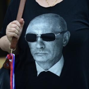 Mulher usa camiseta com foto do presidente russo, Vladimir Putin, em Milão, na Itália