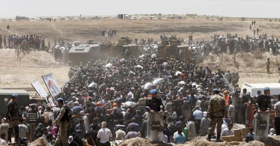 10.jun.2015 - Refugiados sírios esperam para atravessar a fronteira com a Turquia, perto de Akçakale, na província de Sanliurfa, nesta quarta-feira (10). Mais de 230 mil pessoas morreram desde o início do conflito na Síria em março de 2011, de acordo com o relatório divulgado pelo Observatório Sírio dos Direitos Humanos. A crise no país começou com manifestações pacíficas denunciando o regime repressivo do ditador Bashar Assad