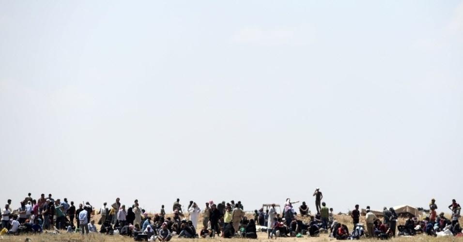11.jun.2015 - Refugiados sírios esperam na fronteira com a Turquia em Akçakale, na Síria. Mais de 2.000 refugiados cruzaram da Síria para a Turquia, fugindo dos confrontos entre combatentes curdos contra o Estado Islâmico (EI) , disse um oficial turco