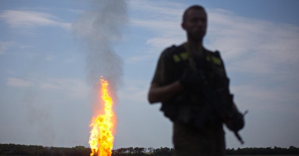 12.jun.2015 - Oficial ucraniano monta guarda enquanto chamas emanam de um gasoduto danificado por bombardeios realizados por separatistas pró-russos, próximo a Avdiivka, na região de Donetsk, no leste do país, nesta sexta-feira (12)