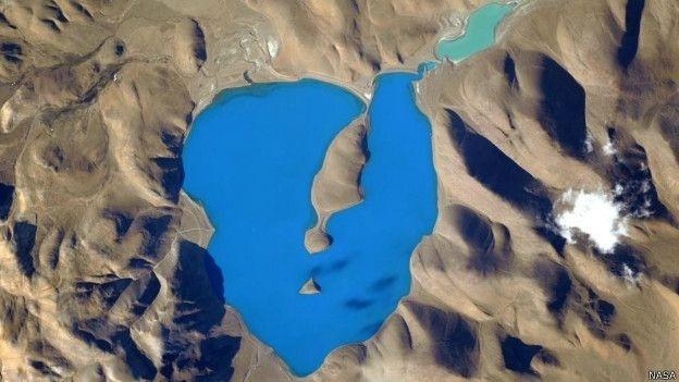 """16.jun.2015 - """"Esse lago no nordeste do Himalaia parece o lugar mais azul do mundo visto da Estação Espacial Internacional"""", escreveu o astronauta americano Scott Kelly em sua conta no Twitter. A foto que acompanha o comentário mostra uma massa de água em forma de coração de um azul tão brilhante que parece modificado pelo Photoshop ou outro programa de edição de imagens. É uma foto do lago Cuo Womo, também chamado de Co Ogma ou simplesmente lago Womo, e o astronauta não mexeu nem um pouco nela ? o lugar é simplesmente assim"""