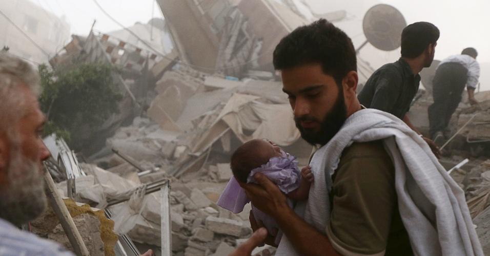 16.jun.2015 - Um homem carrega um bebê salvo de escombros, após um bombardeio realizado por forças leais ao presidente sírio Bashar al-Assad, no bairro de Douma, Damasco (Síria), nesta terça-feira (16)