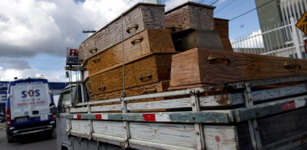 Caminhonete carrega caixões para corpos de presos mortos em presídio de Manaus; ao menos 56 foram mortos no Compaj