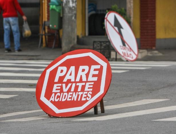 Devido à grande quantidade de acidentes, comerciantes de um bairro na zona norte de SP confeccionaram placas improvisadas para tentar amenizar o problema na região