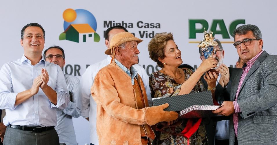 14.ago.2015 - A presidente da República, Dilma Rousseff, ergue imagem de santa durante cerimônia de entrega de 1.480 unidades habitacionais, do programa 'Minha Casa Minha Vida', em Juazeiro, na Bahia