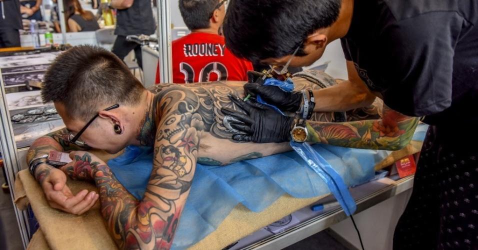 24.out.2015 ? Homem é tatuado durante a Convenção de Tatoo em Nanning, na China, neste sábado (24). Em 2015, a convenção anual acontece entre os dias 23 e 25 de outubro