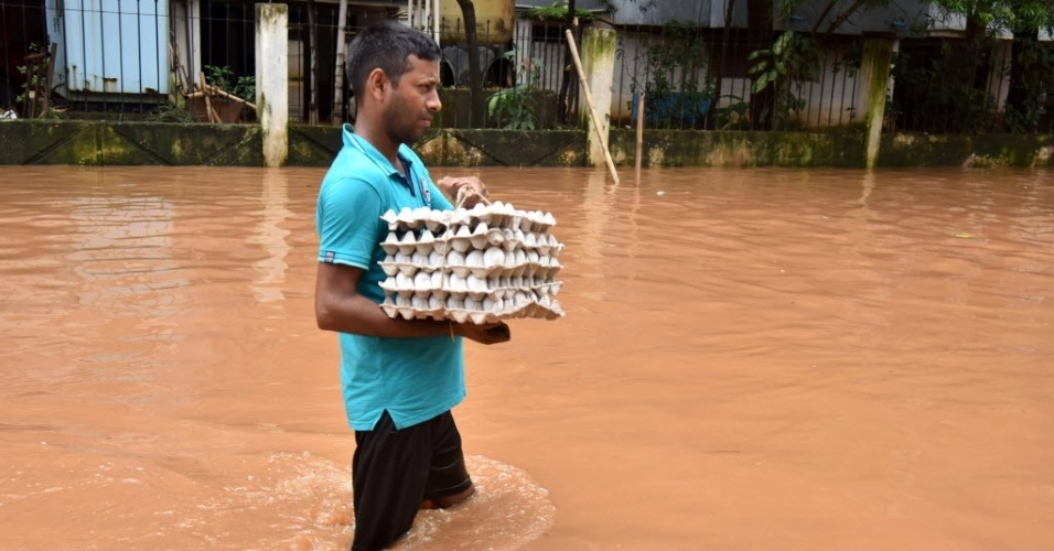 19.jul.2016 - Um homem  carrega uma bandeja de ovos enquanto tenta atravesssar uma área inundada na cidade de Guwahati. Provocadas pela monção anual, as inundações no Estado de Assam, na Índia, afetaram milhares de pessoas que vivem em seis distritos